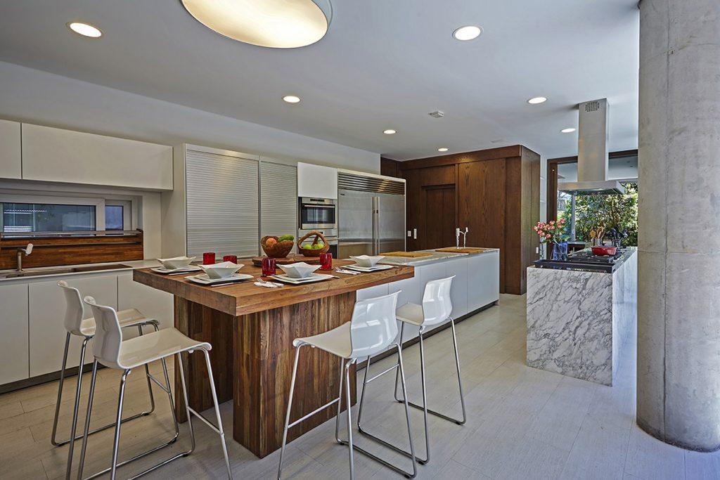La cocina, de Bulthaup, cuenta con un comedor auxiliar de madera tipo barra y sillas de Ikea. El piso es de porcelanatto con textura tipo madera, de Espacios & Soluciones. Fotografía: Gabriel Lugo.