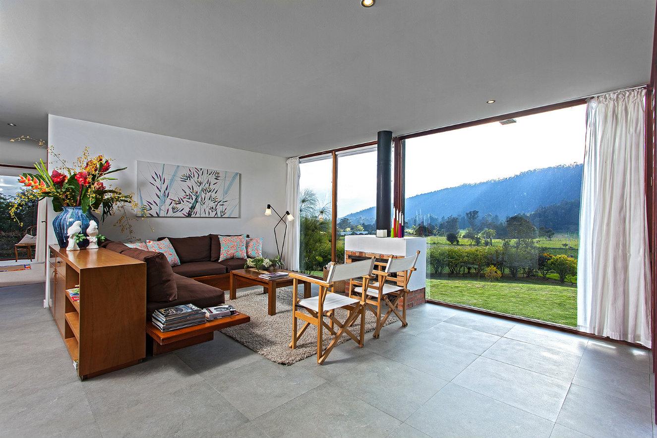 Para la sala, con chimenea y vista a la Sabana, se escogió un sofá con base de madera y cojines sueltos, y sillas tipo director. El piso es de porcelanato y el gran florero azul, de cerámica. Fotografía: Luis Gabriel Lugo.