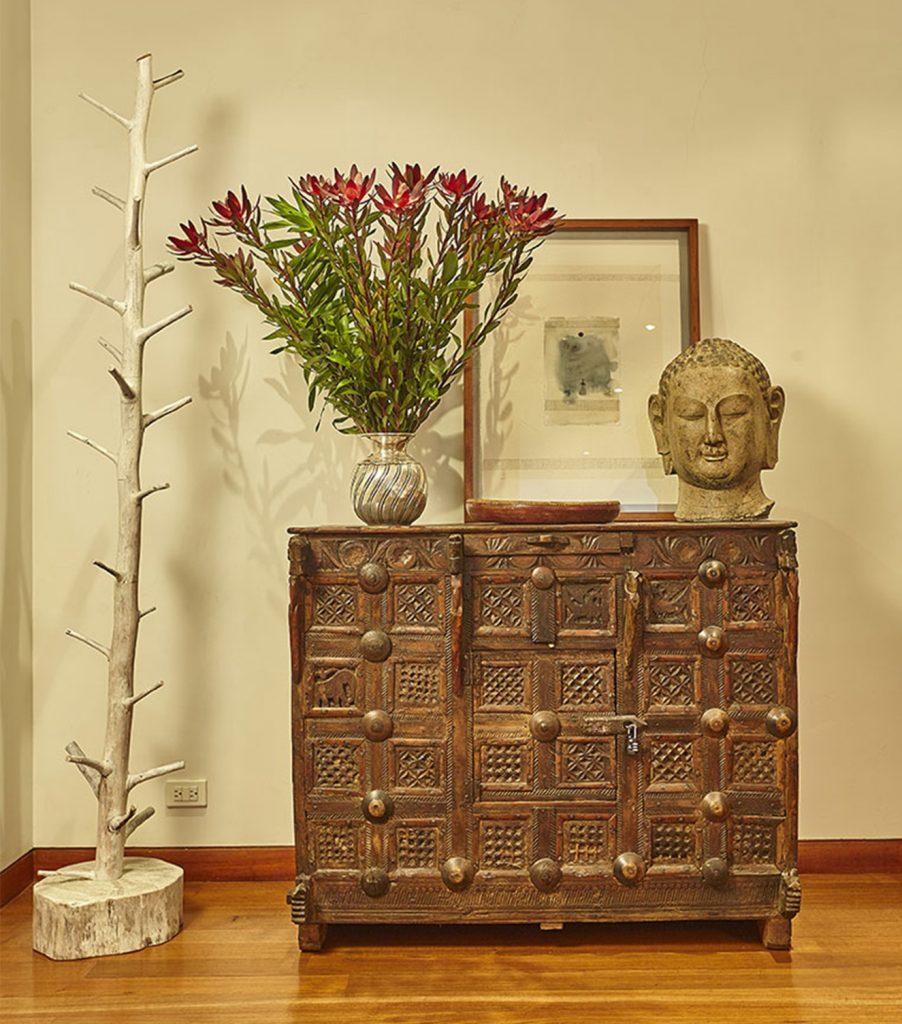 Sobre el mueble asiático, de Arte y Ritual, cabeza traída de la India. El perchero fabricado en Ubaté está hecho a partir de una penca de cactus. Cuadro de Denise Buraye. Fotografía: Gabriel Lugo.