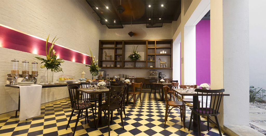 El restaurante Clemente exhibe un elegante piso ajedrezado que contrasta con los detalles de color en el nicho y la pared.